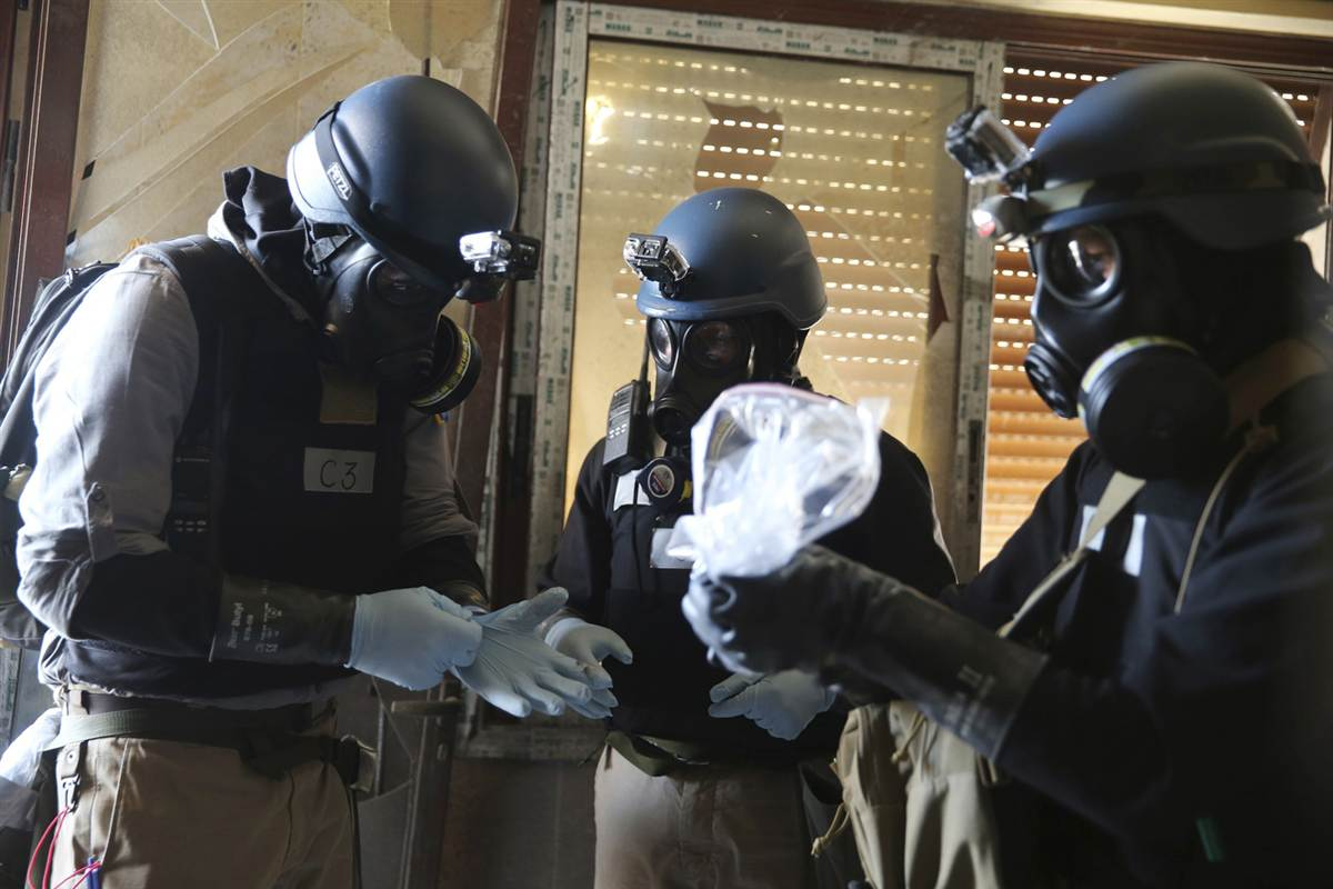 A U.N. chemical weapons expert holds a plastic bag containing samples from one of the sites of a chemical weapons attack Photo by Mohamed Abdullah