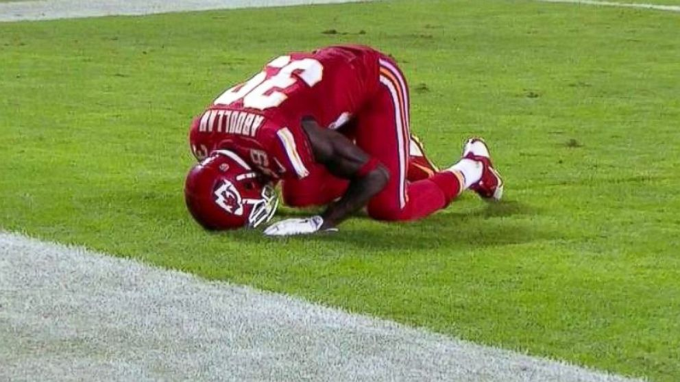 Abdullah kneeling in prayer after scoring a touchdown Media by ABCnews.com