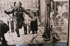 Soldier jumping over barbed wire from East Berlin to West. Source: russiawithlove.blogspot.com