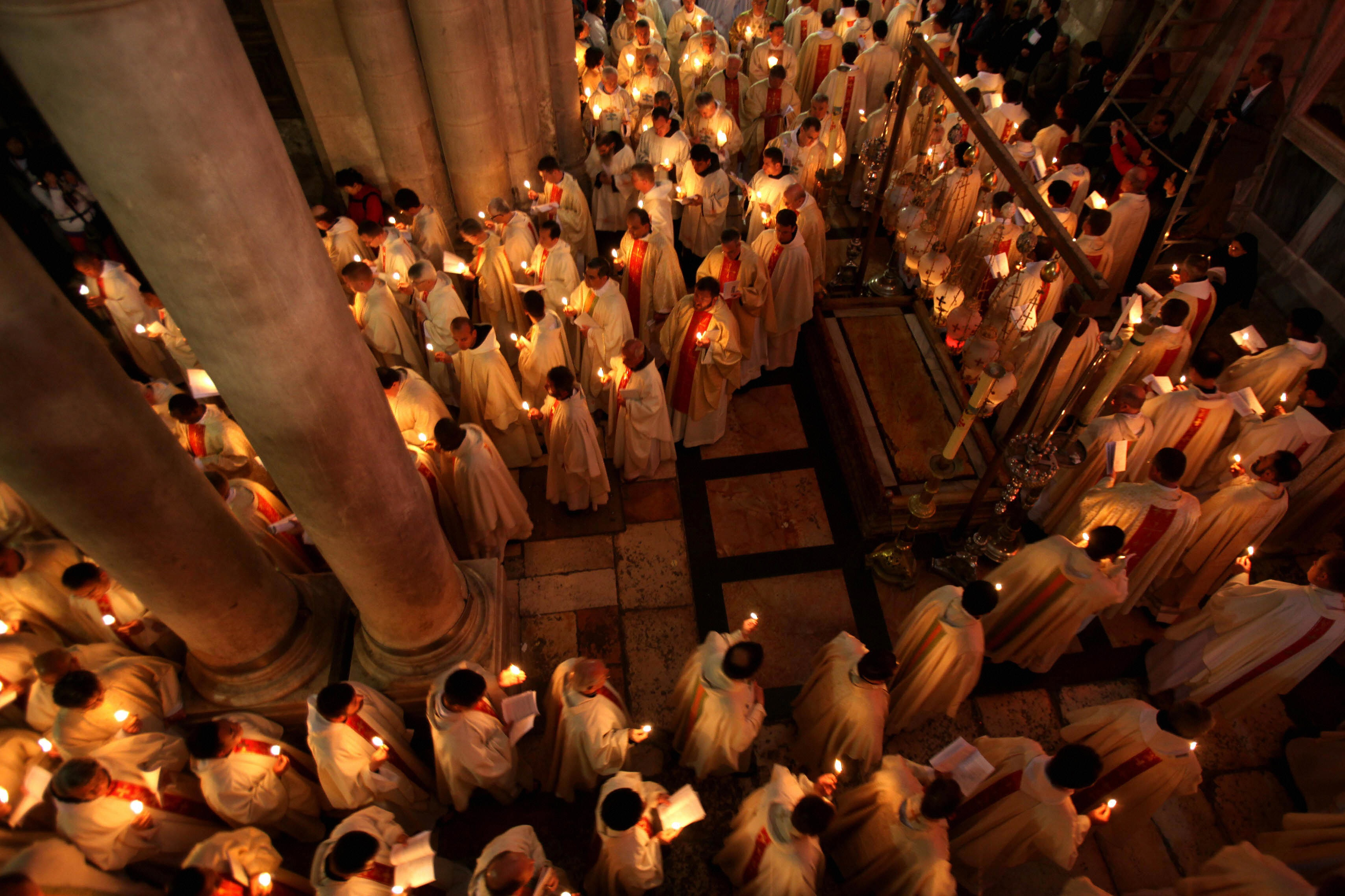 Roman Catholic clergy men hold candles as they circle the aedicule on Holy Thursday. Many Christians believe that  the Church of the Holy Sepulchre in Jerusalem is where Jesus was crucified and buried. Source:http://www.cnn.com