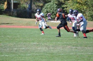 Jacob Battaglia tries to evade a couple defenders. Photo from Greenville College Football