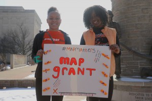 Students hold a sign outside the Capitol building to protest the MAP grant bill