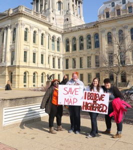 Four students hold up sign to save the MAP grant