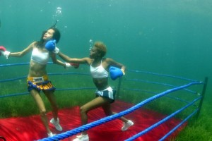 Ladies taking punches at each other in a underwater boxing match. Image from creativeherald.com