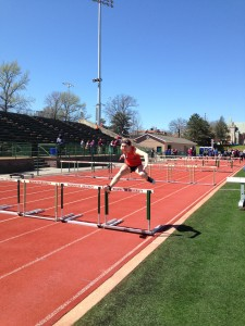 Gabby Adam hurdling over a hurdle in the 110 meter hurdler women's race. Image by Austin Brinkman