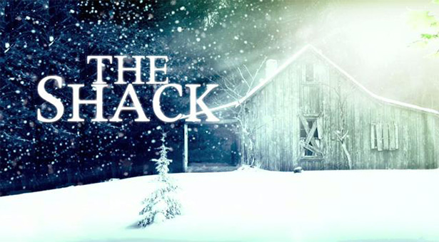 A snow covered old barn at night with the words