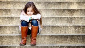 Little girl sitting on steps, sad