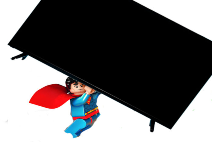Lego Superman holding up a TV