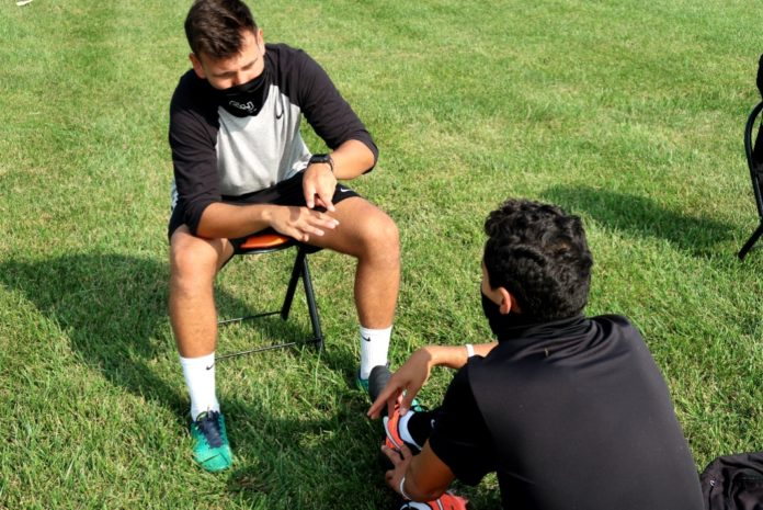 Coach Bueno talking to a soccer player. Media by Jose Soutullo